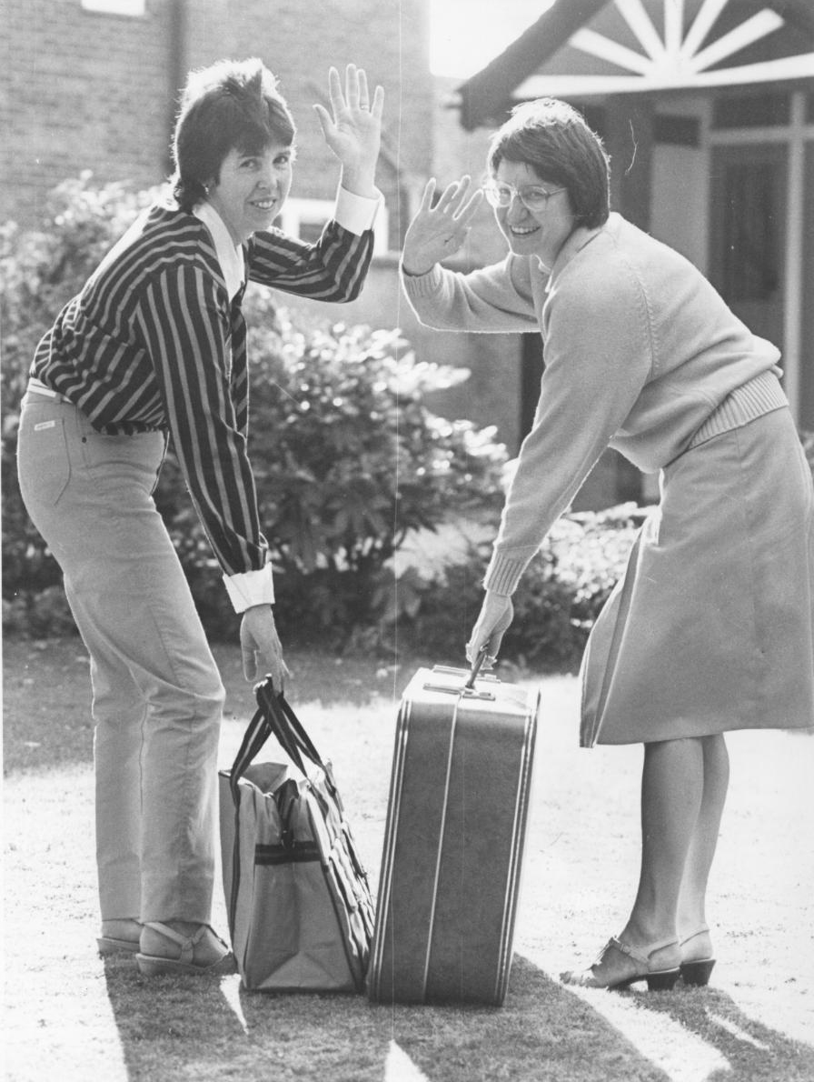 Black and white image of two WI members with suitcases in their hands