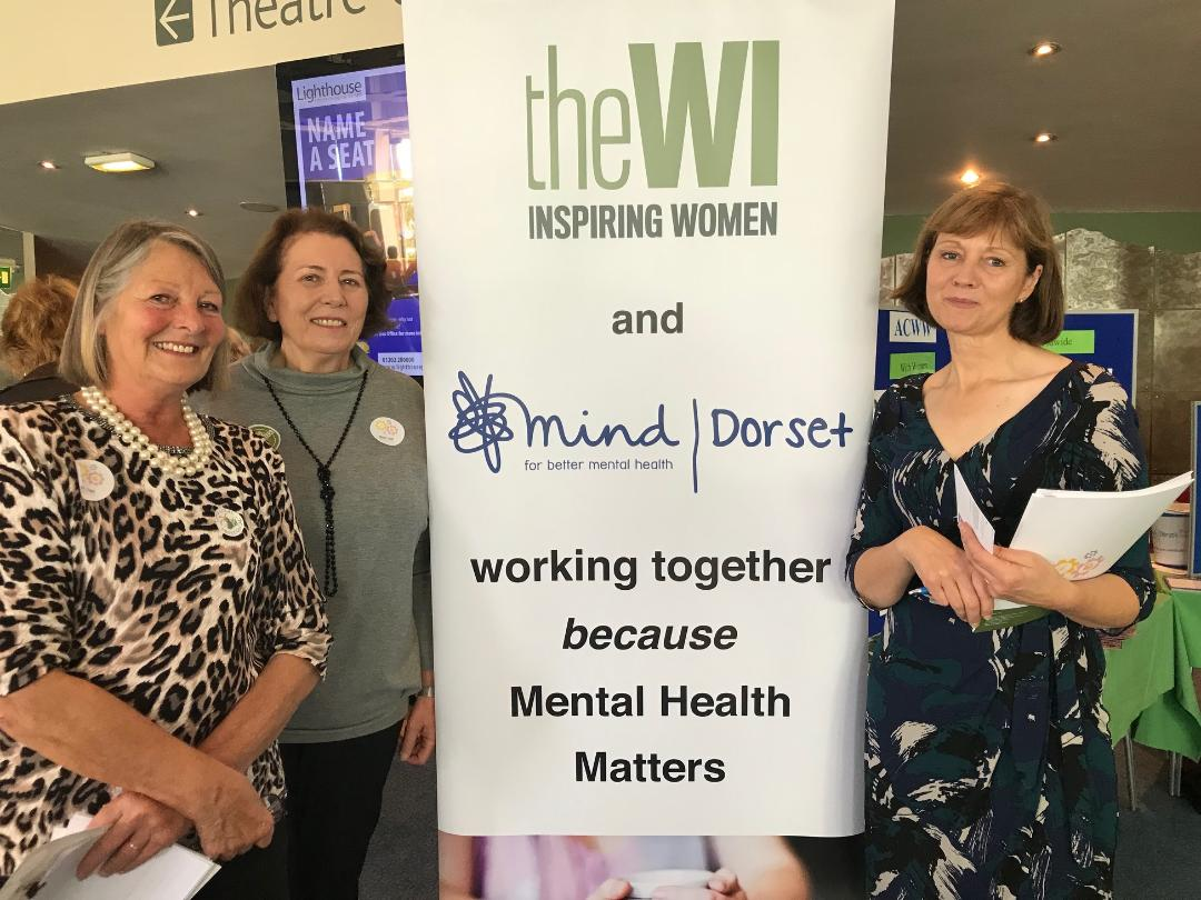 """Three women standing next to a banner that reads """"The WI and mind 
