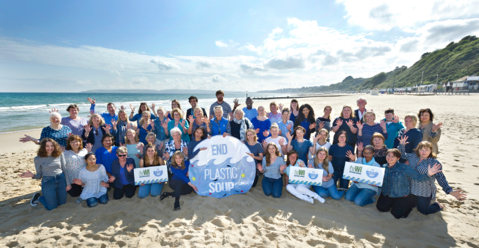 """A large group of women on the beach holding up blue/white """"End Plastic Soup"""" banners"""