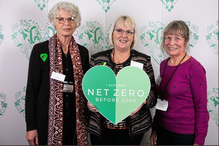 3 women standing next to each other with the one in the middle (Ann Jones) holding a green heart made of carton