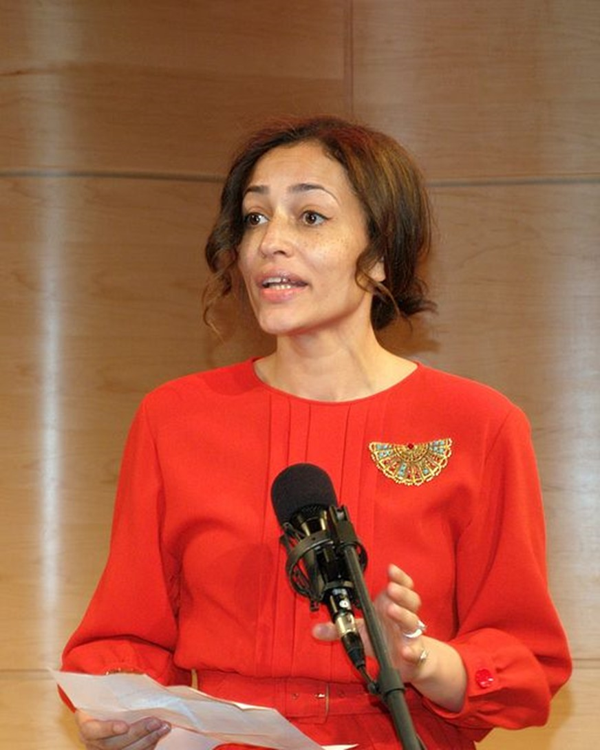 Zadie Smith standing behind a microphone and speaking while holding a piece of paper