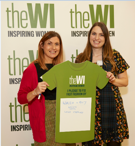 """Two women at a WI event holding up a green sign in the shape of a tshirt that reads """"I pledge to fix fast fashion"""""""