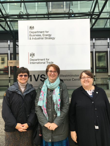 3 women standing outside, in front of the Department for Business, Energy & Industrial Strategy