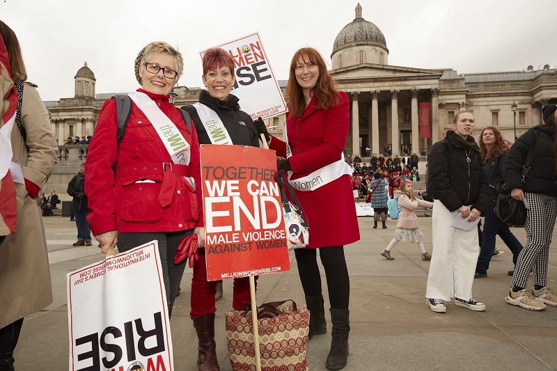 Three WI members with signs at the Million Women Rise march in London 2020