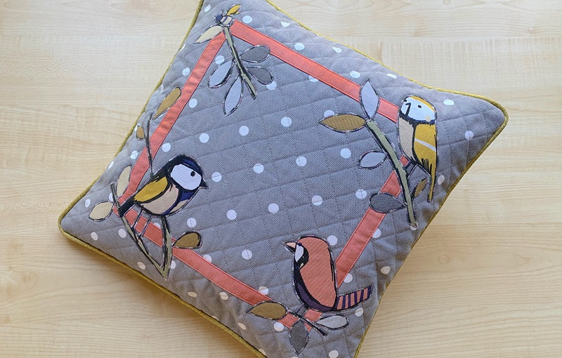 A blue cushion cover with dots and birds