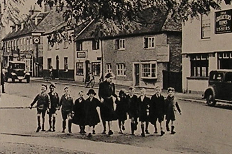 Evacuee children being escorted down a village street