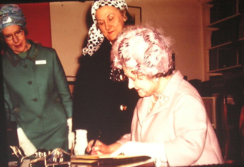 Queen Mother signs the visitor's book at Denman College