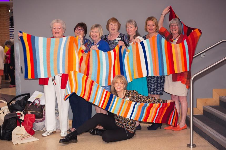 Women holding up a multicolored scarf