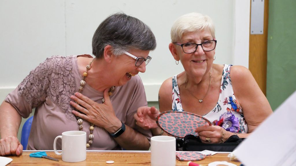 Members crafting and laughing at a WI meeting