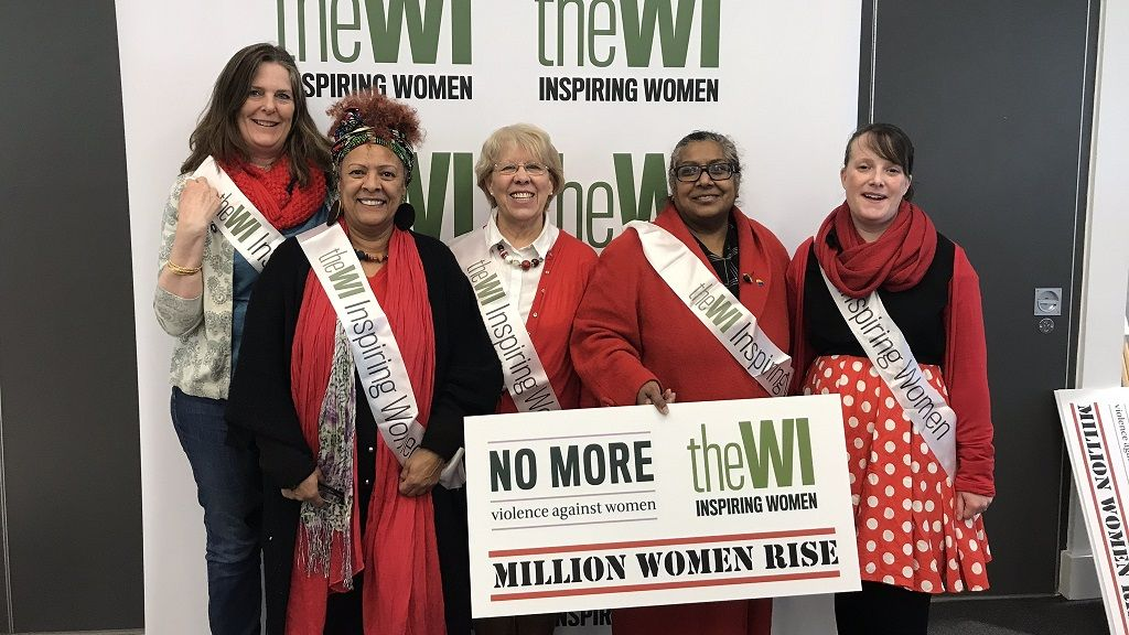 A group of women in front of a WI Logo wall at the Million Women Rise March 2020
