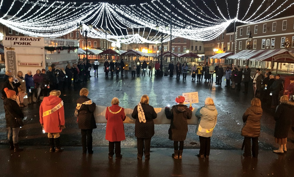A large group of women standing outside at an event/protest held at a Christmas Market