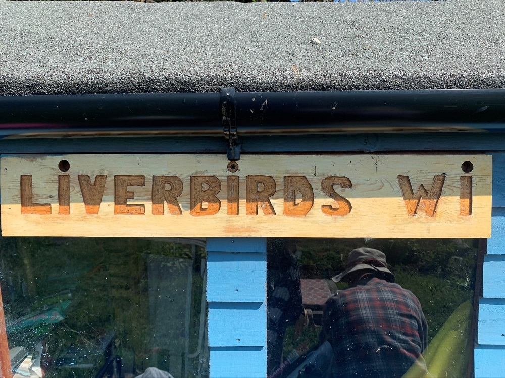 A wooden sign that reads Liverbirds WI
