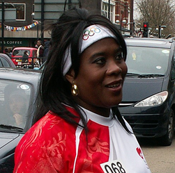 Tessa Sanderson on the street wearing a sports outfit giving an interviiew