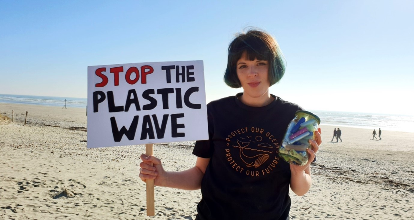 Picture of Ella Daish on the beach holding a sign that reads 'Stop the plastic wave