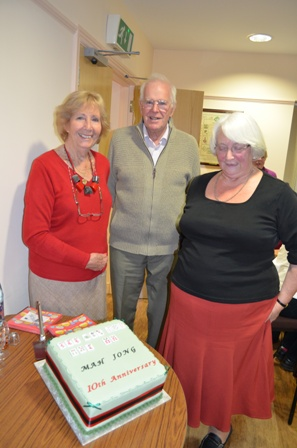 Photo shows Shirley Corke, County Chairman, with her husband Peter Corke and member of Mahjong group with the celebratory cake