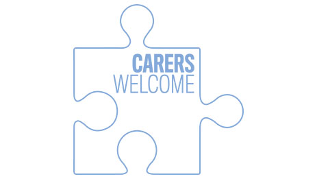 A white/blue piece of a jigsaw puzzle; Carers Welcome written on it