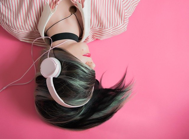 A woman lying on the floor with headphones on