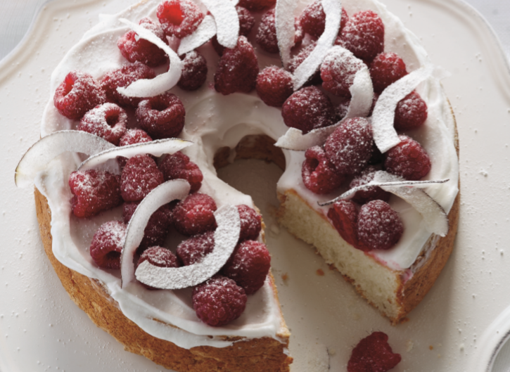 A cake decorated with raspberries and coconut