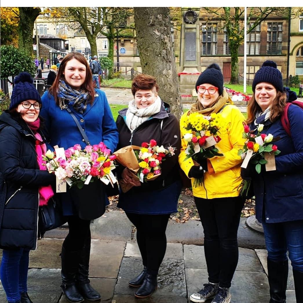 Five women standing outside holding flower bouquets