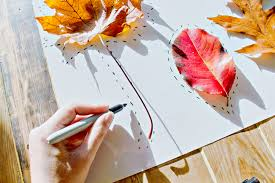 Picture of a hand holding a pen drawing autumn leaves