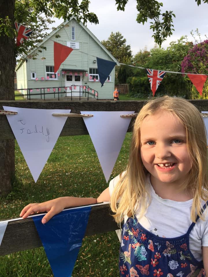 A girl standing next to bunting at a fence