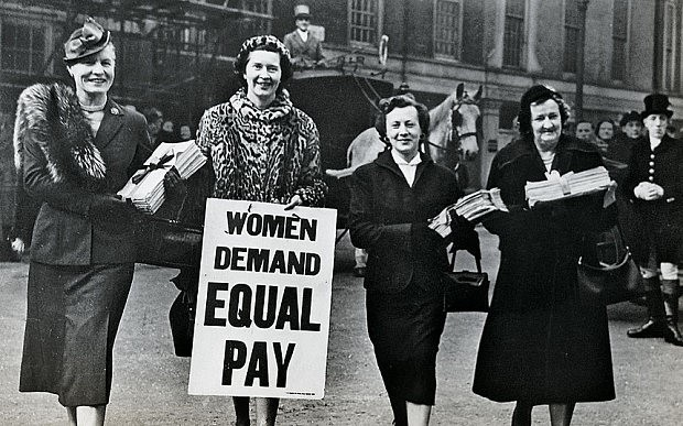 "Four women next to each other with one holding up a sign saying ""Women demand equal pay"""