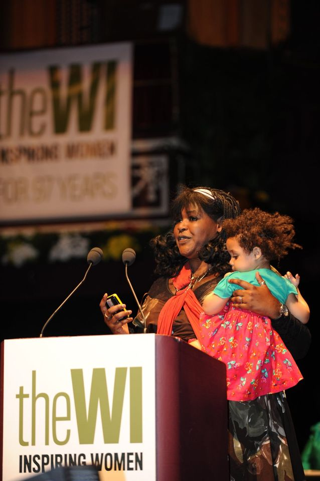 Dr Aderin-Pocock on stage at the NFWI Annual Meeting, speaking and holding a child in her arms