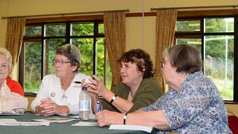 WI members gathered around a table discussing
