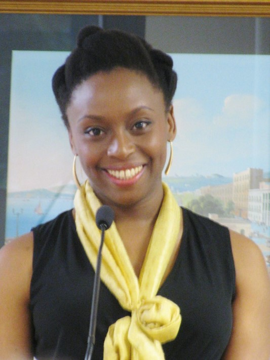 Chimamanda Ngozi Adichie standing behind a microphone smiling towards the camera